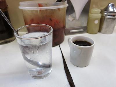 お冷に入れられたスプーンとデミタスカップのコーヒー