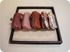 a selection of clutches. all woven in different materials. Check out the tray's edge– it's woven too!