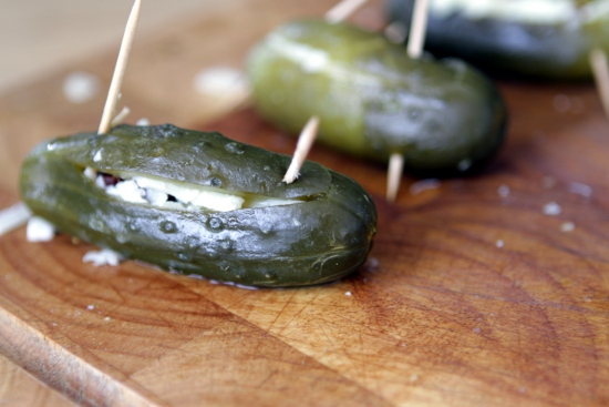 Dill pickles stuffed with cheddar cheese and bacon and resealed with toothpicks.
