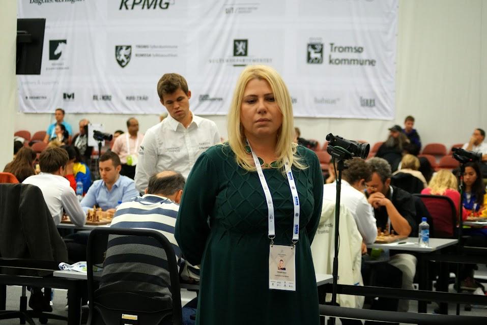 Susan Polgar observa las partidas mientras Magnus Carlsen hace lo propio en las mesas de atrás.
