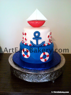 Two tier blue, white and red nautical fondant baby shower cake with anchor, life preservers, waves, fondant pearls and sailboat topper