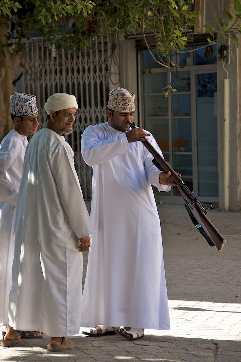 Omani men inspect rifle