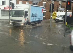 Lorry ploughing through a foot of storm water