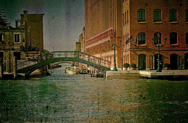 Vista sobre um canal com um barco ancorado e uma ponte de passagem por cima do canal.