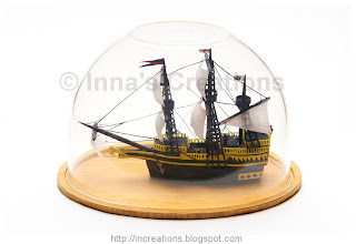 Miniature galleon under a display dome