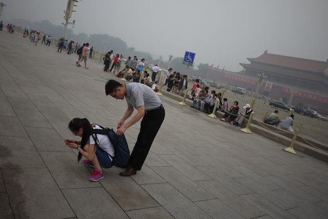 young man checking a young woman's backpack at Tiananmen Square