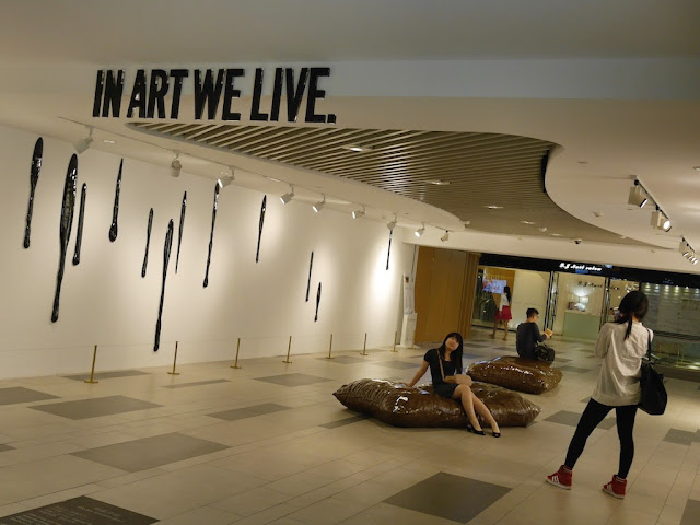 Young woman being photographed in an art installation with the words 'In Art We Live.""