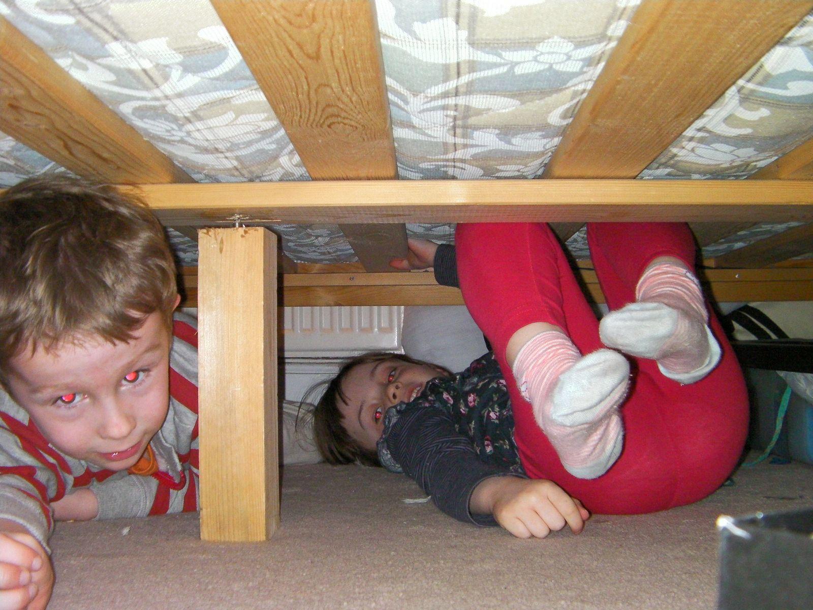 kids hiding under a bed wooden support strut