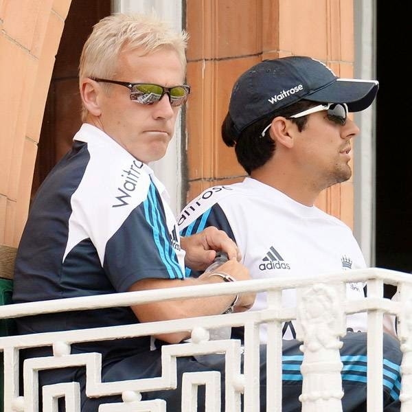 England's captain Alastair Cook sits with coach Peter Moores (L) on the dressing room balcony during the second cricket test match against India at Lord's cricket ground in London July 21, 2014.