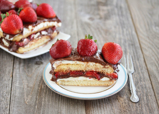 photo of a slice strawberry tiramisu on a plate with the rest of the cake in the background