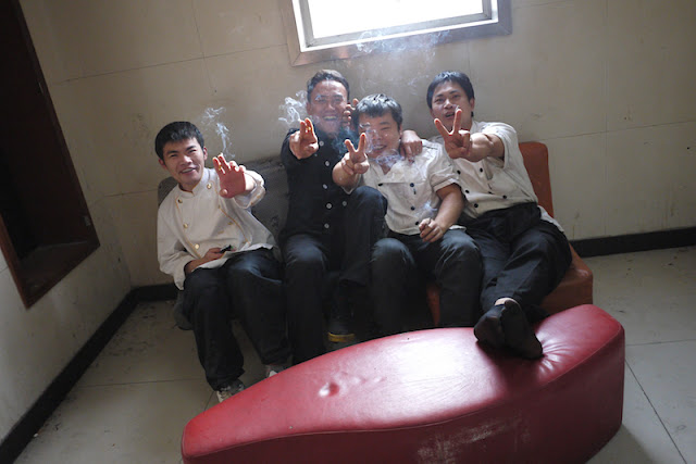four men smoking while sitting on a small sofa in Changsha, China