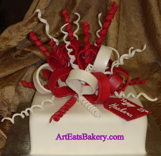 Square white fondant custom unique birthday cake with red and white ribbons and bows