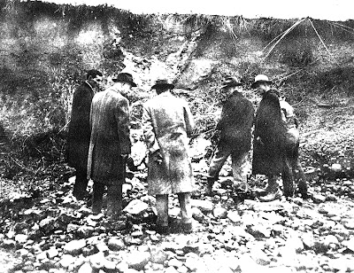 A winter flood dig out the bank of Deer Creek and exposed the outline a prehistoric iron furnace pit.  Arlington Mallery, who was investigating these in 1949-1950, is second from left in the group of men who came to investigate.  This photo appeared in the Chillicothe Gazette and likely was taken by paper's Marcus Orr .