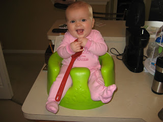 Cute child sitting on counter in a bumbo seat.