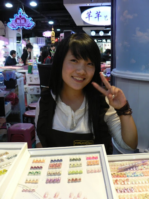 young woman in Shenyang sitting behind a table of numerous fake nails with a variety of designs