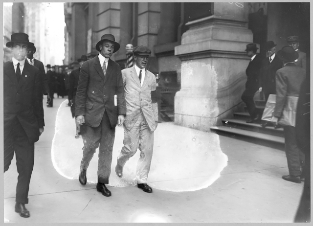Author Upton Sinclair, in white suit with black arm band, picketing Rockefeller Building