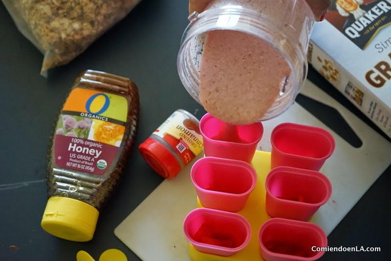 Ponemos trocitos de fresas en los moldes y agregamos la mezcla. Congelar. #QuakerUp