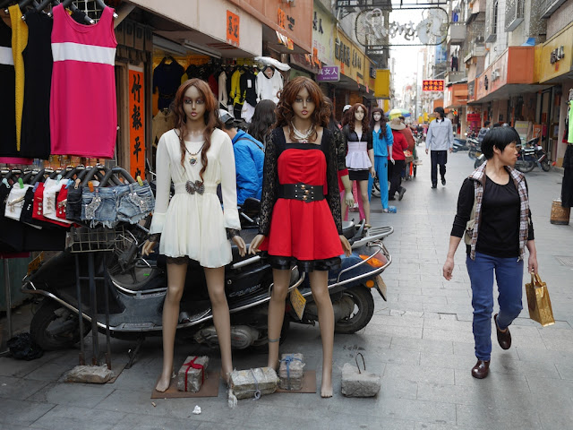 mannequins and woman walking by in Yangjiang, China