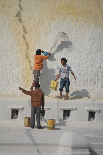 3 workers whitewashing the stupa