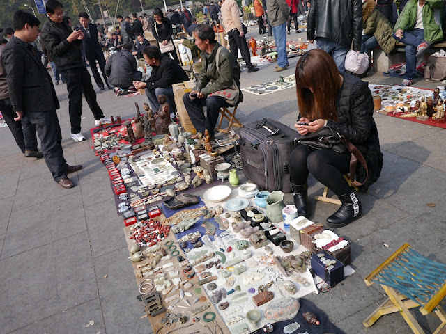 woman looking at her mobile phone at an outdoor antique market in Changsha, China