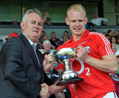 Cork Captain Cáthrach Keane receives All Ireland JF C Cup from Christy Cooney.
