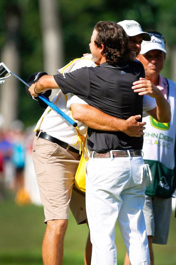 Brian Harman embraces his caddie Scott Tway after winning the John Deere Classic held at TPC Deere Run, on July 13, 2014, in Silvis, Illinois.