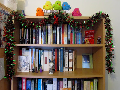 Bookshelf decorated with tinsel