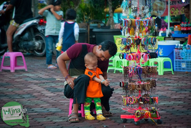 penjual aksesoris mengasuh anak di Tepian Sungai Musi Palembang tahun 2015