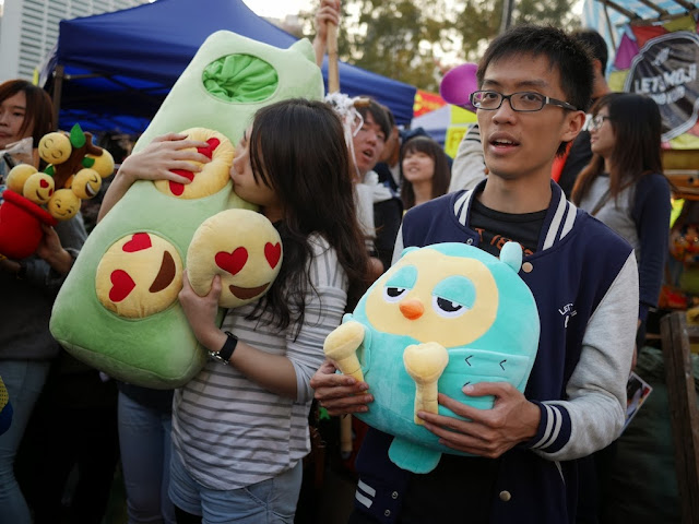 two college students hold stuffed toys
