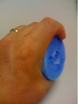 Picture of a piece of swimming noodle cut and fitted inside the hand of a learn to swim freestyle swimmer