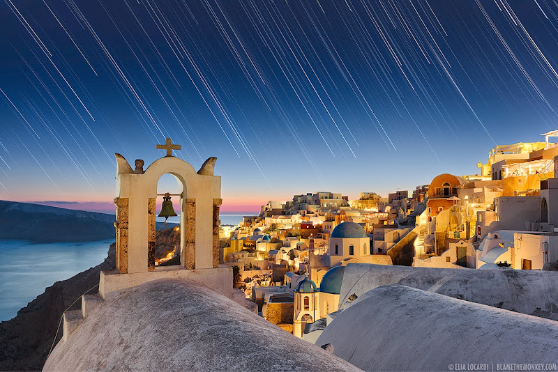 The stars dance above the enchanting town of Oia Santorini, the island paradise of the Aegean Sea. Photographer Elia Locardi