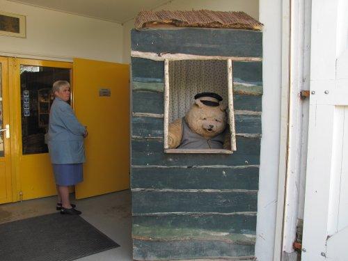 Bruin de beer zit aan de ingang