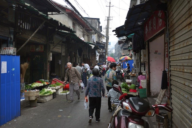 man walking with a cane next to vegetables for sale at Beizheng Street in Changsha, China