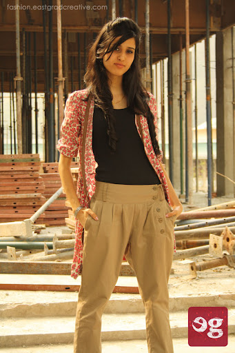 Layered top, pleated trouser pant and a pair of flat pump shoes.