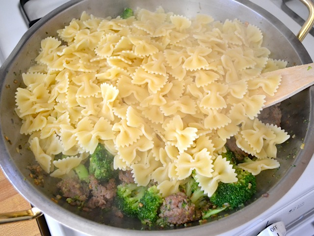 drained and cooked pasta added to broccoli and sausage in skillet