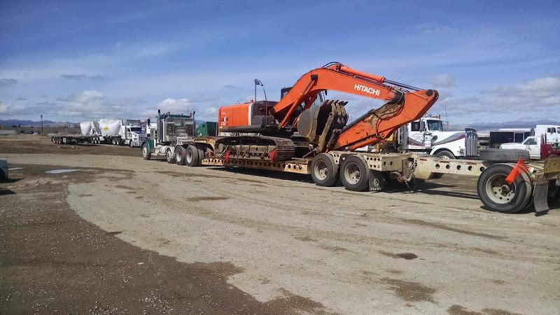dropdeck flatbed trailer loaded with orange Hitachi backhoe excavator