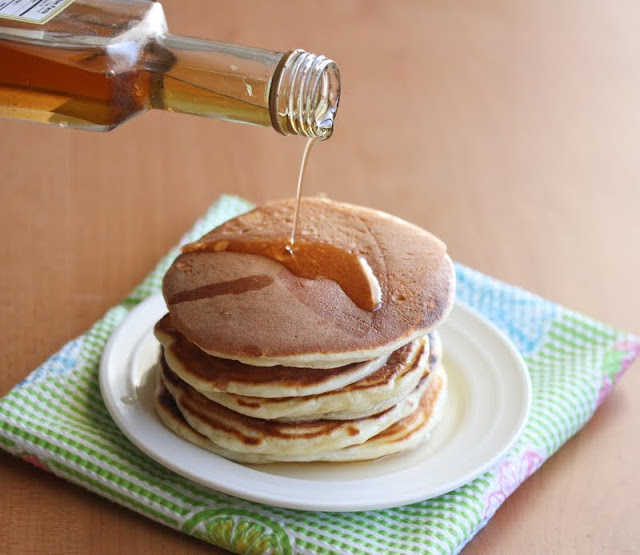 photo of syrup being poured over a stack of pancakes