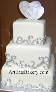 Three tier unique custom white wedding cake design with silver curlicues and edible hearts topper idea picture