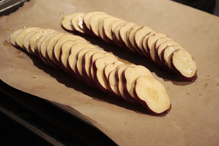 Sliced, fanned sweet potatoes on baking sheet