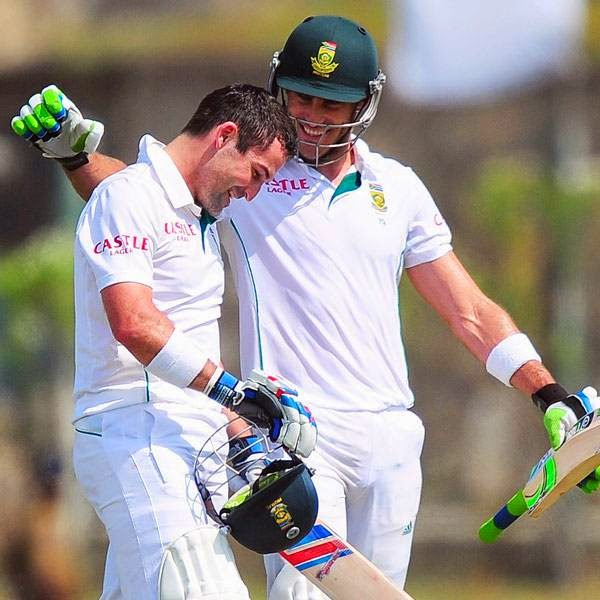 South Africa cricketer Dean Elgar (L) is congratulated by his teammate Faf du Plessis (R) after scoring a century (100 runs) during the first day of the opening Test match between Sri Lanka and South Africa at the Galle International Cricket Stadium in Galle on July 16, 2014.