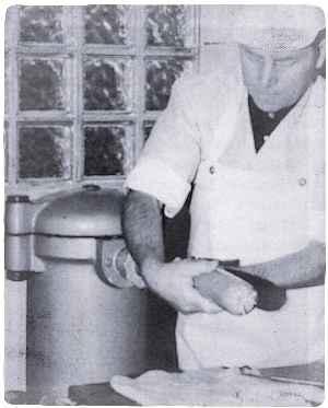 Hausschlachtermeister Otto Böke (Leopoldstal) bei der Arbeit. Ihm stehen in seiner Wursteküche moderne Geräte — hier die elektrisch betriebene Wurst-Füllmaschine — zur Verfügung. Foto: Wiemann