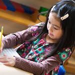 Montessori kindergarten student at the Huntington Beach Harbor campus practicing cursive handwriting