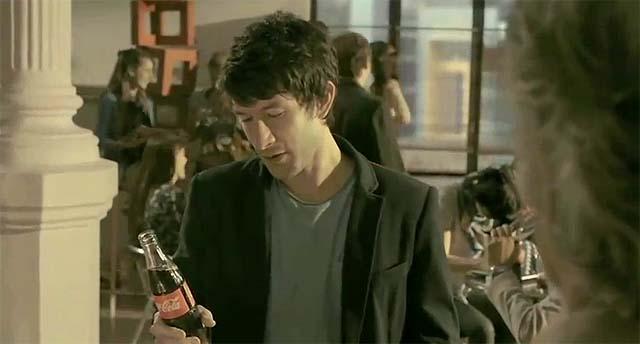 Hombre mirando una botella de Coca-Cola