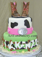 Two tier cowgirl unique creative birthday cake with handmade edible boots topper, pink belt, fence, flowers and name in cow print