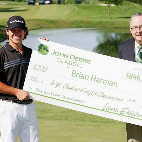 Sam Allen, Chairman and CEO of Deere & Company, presents the winners check to Brian Harman, winner of the 2014 John Deere Classic, held at TPC Deere Run, on July 13, 2014, in Silvis, Illinois.