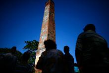 Un grupo de personas observa la chimenea.