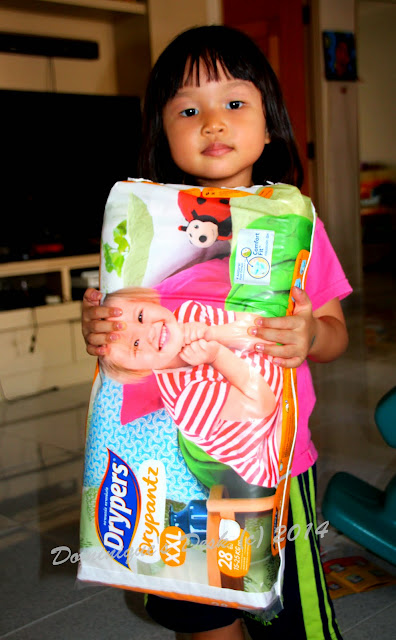 Tiger girl holding her pack of Drypers Drypantz
