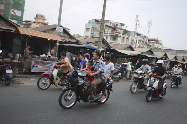 two men and a boy riding a motorbike by a market