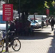 Straßenszene mit roten Wahlplakaten der DKP: »Nieder mit der Festung Europa! DKP«.
