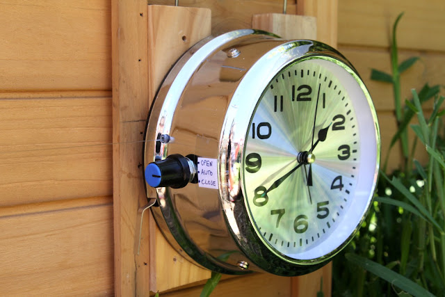 The automatic chicken door opener clock mounted on the coop